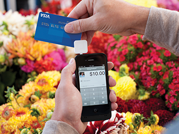 Making payment with Visa card in flower market using Square on mobile phone.