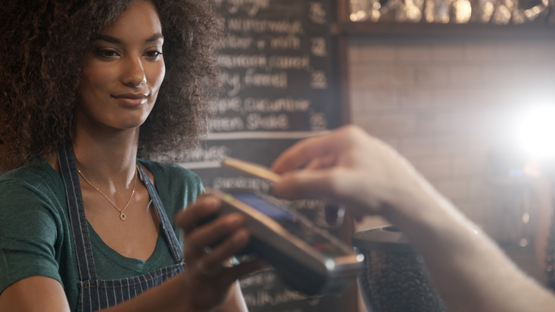 A barista accepting a customer payment via a smart phone at a POS device.