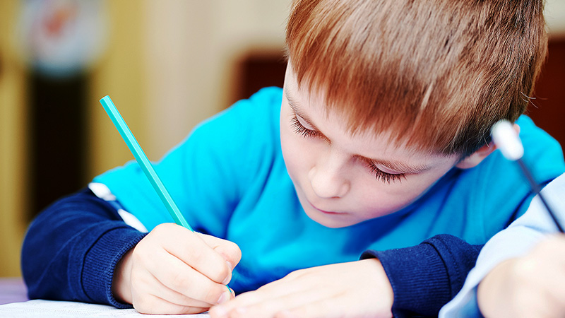 Young boy wearing blue focusing on writing on a piece of paper.