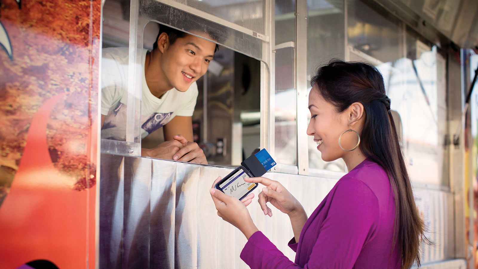 Woman using a mobile card reader to make purchase at food truck.
