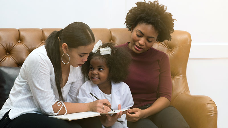 A Black female LGBT couple and their child sit on the couch working on her homework.