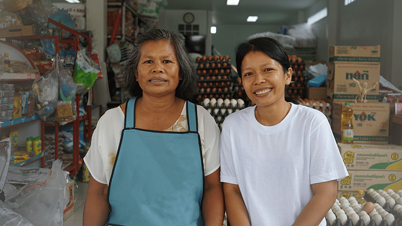 Two woman smiling, looking at the camera standing inside a grocery store.