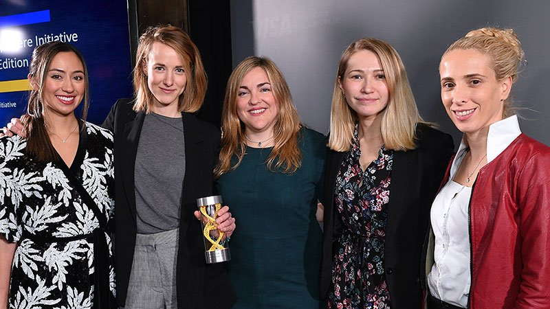 Five women entrepreneurs arm-in-arm with one holding a trophy.