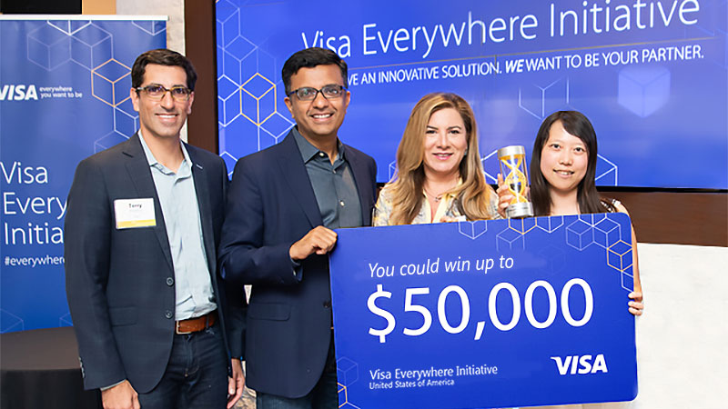 "Four people standing in front of a blue screen holding a card that says ""You could win up to $50,000"""