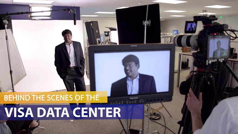 Behind the scenes of Visa Data center with cameras in the background and a man facing the cameras.