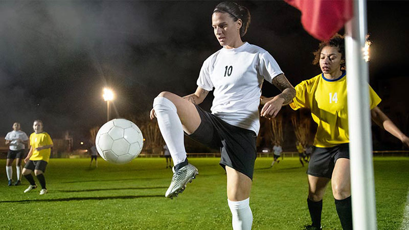 Dzsenifer Marozsán kicking a football in a game as another football player runs up behind her.