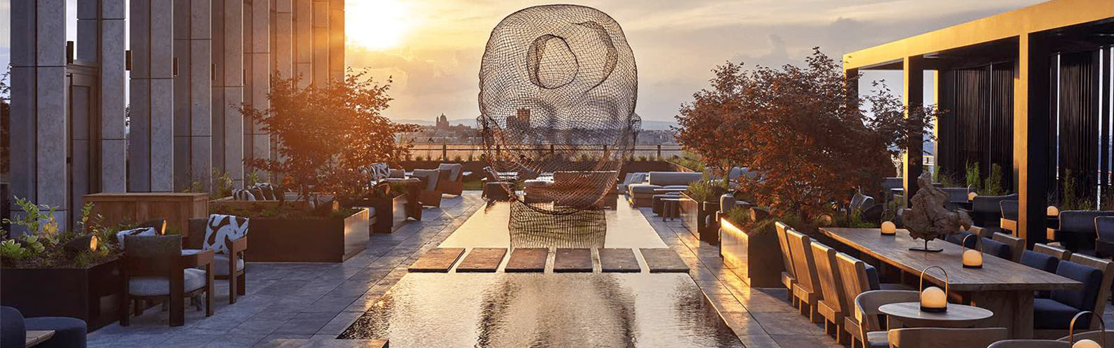 Dazzling view of the sunset from the balcony of the Equinox Hotel with multiple cozy seating areas and a modern wire sculpture over a water feature.