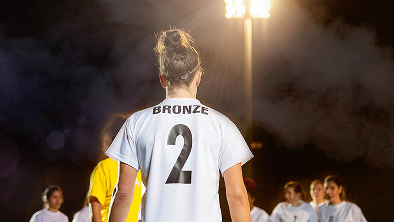 The back of Lucy Bronze as she faces the field wearing her jersey with the number two on it.