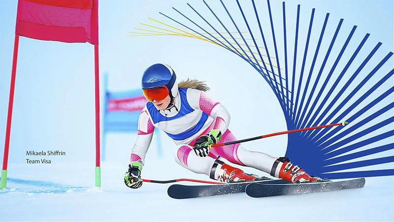 Olympian and Team Visa member Mikaela Shiffrin skis down a slope and around a flag.