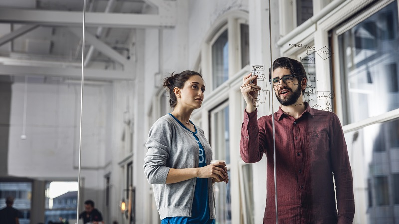 Man and woman discussing diagram on glass wall