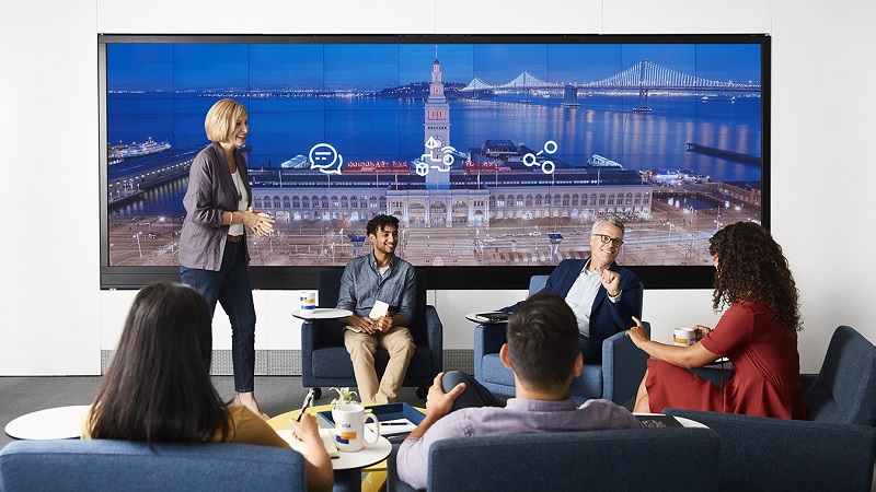 Six men and women talking and sitting on chairs in front of large tv screen