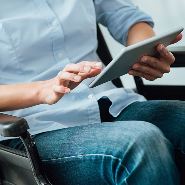 A person sitting down and holding a tablet.