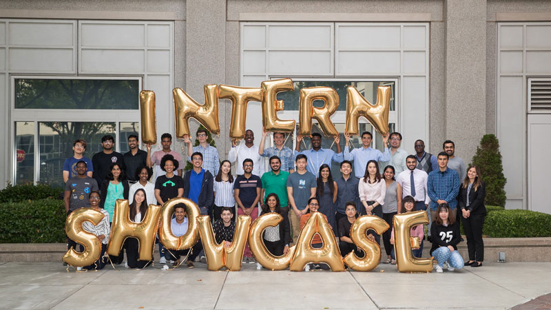 "A group of interns hold balloons that spell out the words ""Intern Showcase""."