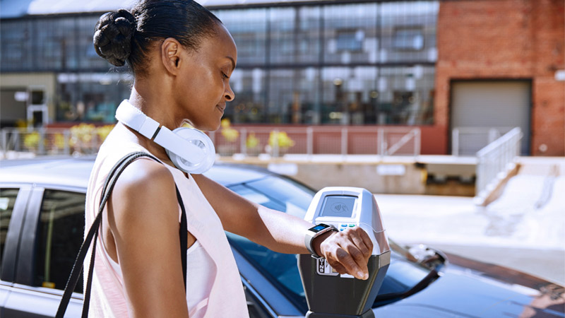 Woman standing in front of a parked car while looking at her Fitbit.