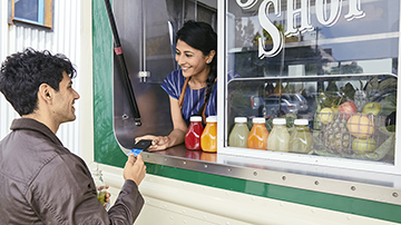 A young man makes at contactless payment with his Visa card at a juice shop.