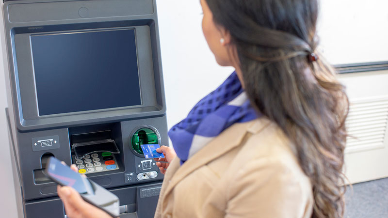Woman using her card near an ATM and a holding a phone in her other hand.
