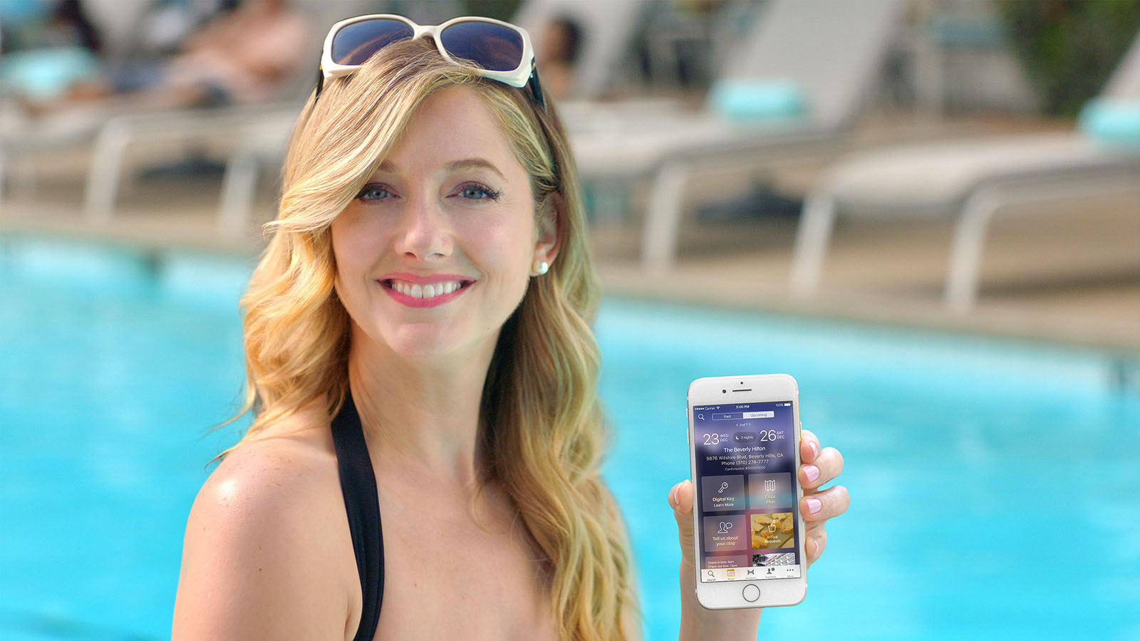 Woman next to pool holding smartphone