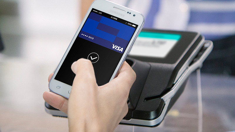 A hand holding a mobile phone over a POS using mobile payments.