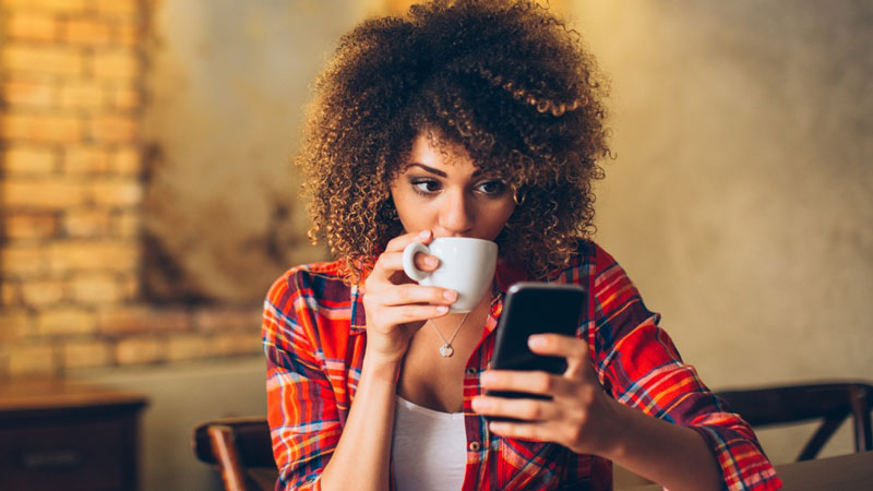 Woman drinking her coffee and checking her phone