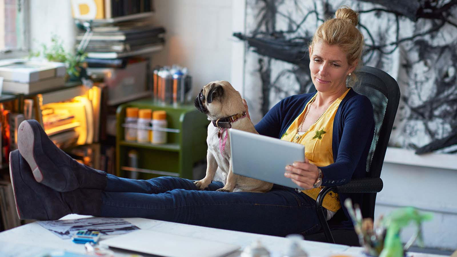 Woman with her feet on a desk and a dog in her lap reading a tablet.