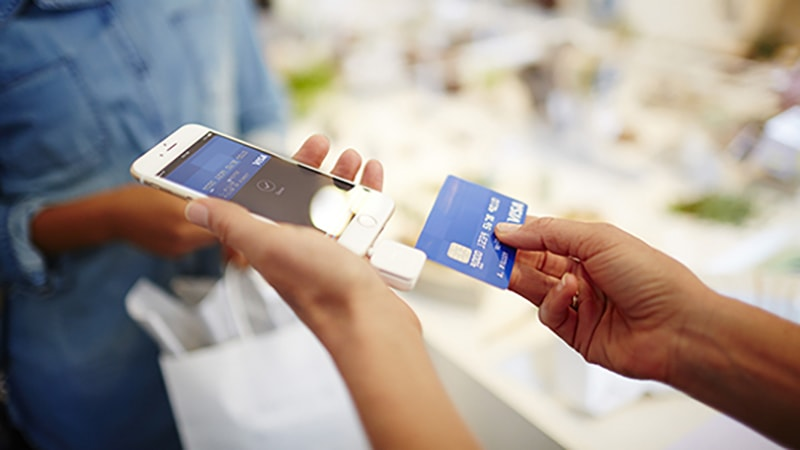 Merchant using Square Credit Card reader to swipe Visa card for purchase.