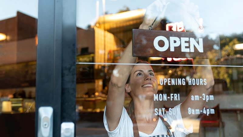 "A young woman puts up an ""open"" sign in the window of a small business."