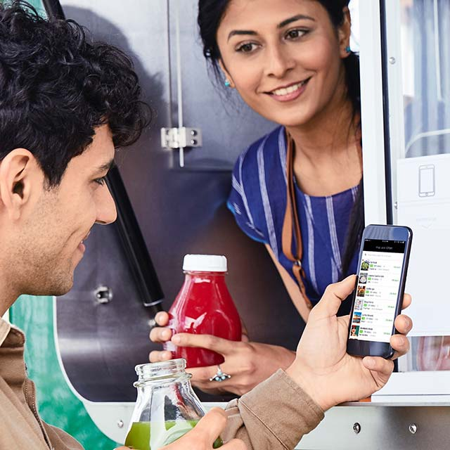 Man looking at his mobile phone while standing near a food truck and woman smiling and serving him some sauce.
