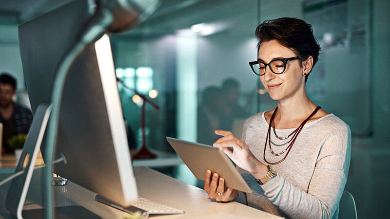 A woman smiling using her tablet in the office.