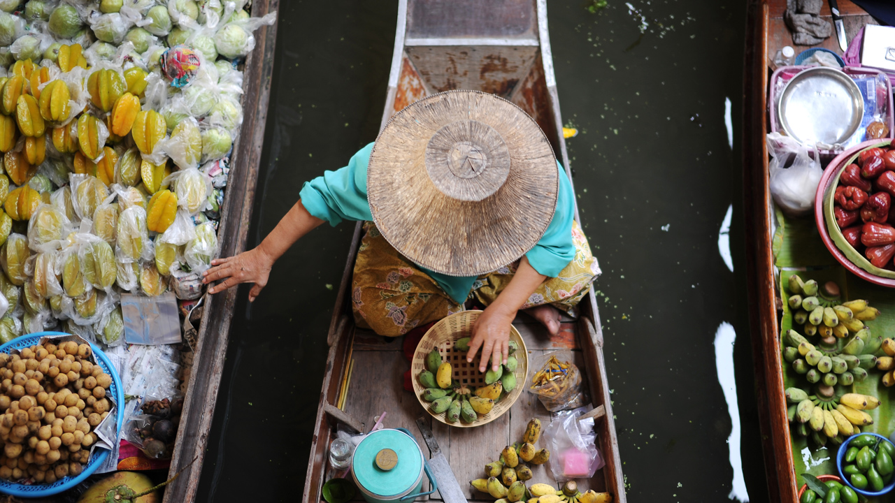 Top view of a person wearing a wide-brimmed hat, sitting in a canoe filled with fruits.