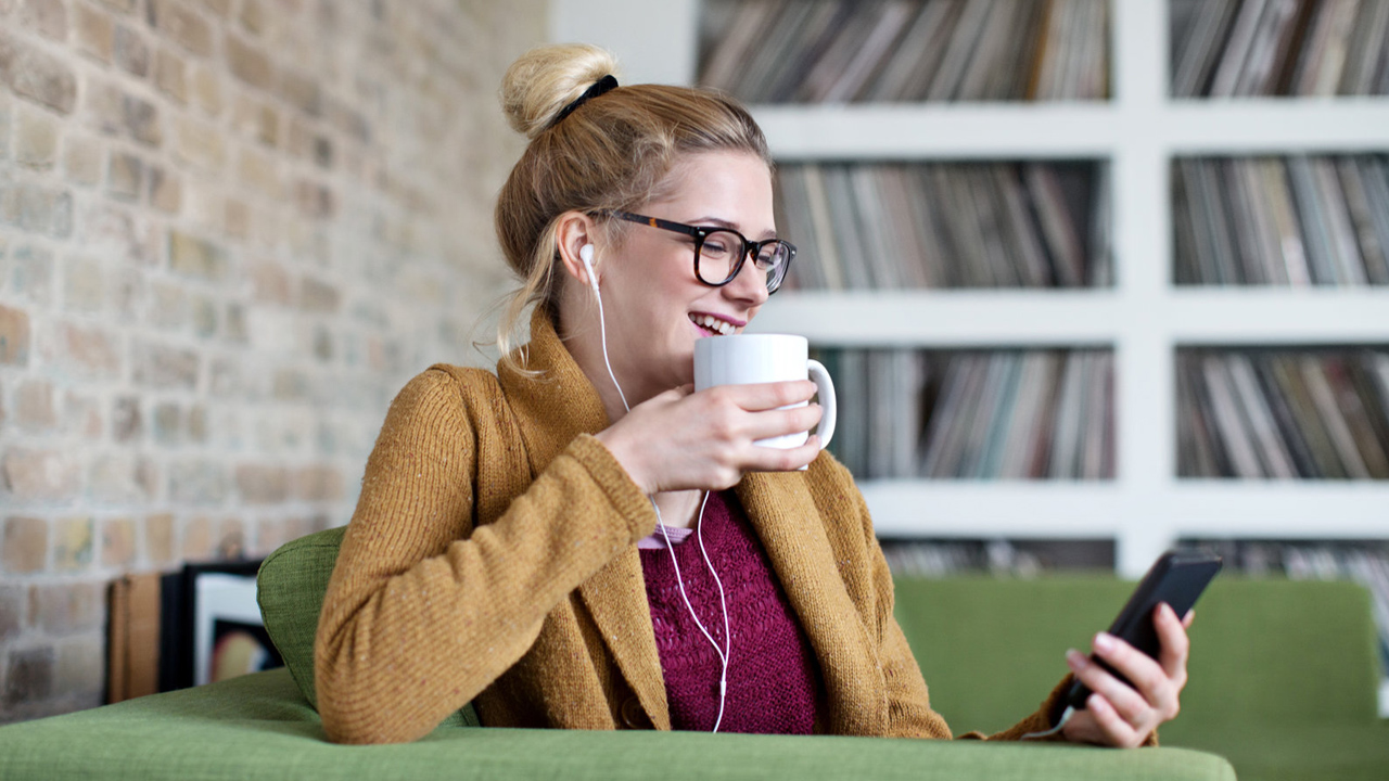 A smiling woman sitting on a couch with earphones on while holding a mug in one hand and a phone on the other.
