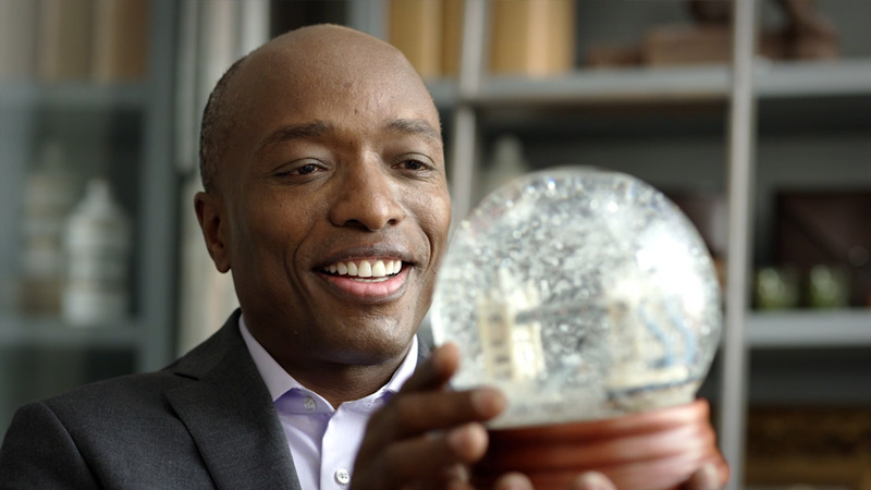 A man admiring a snow globe in his hands.