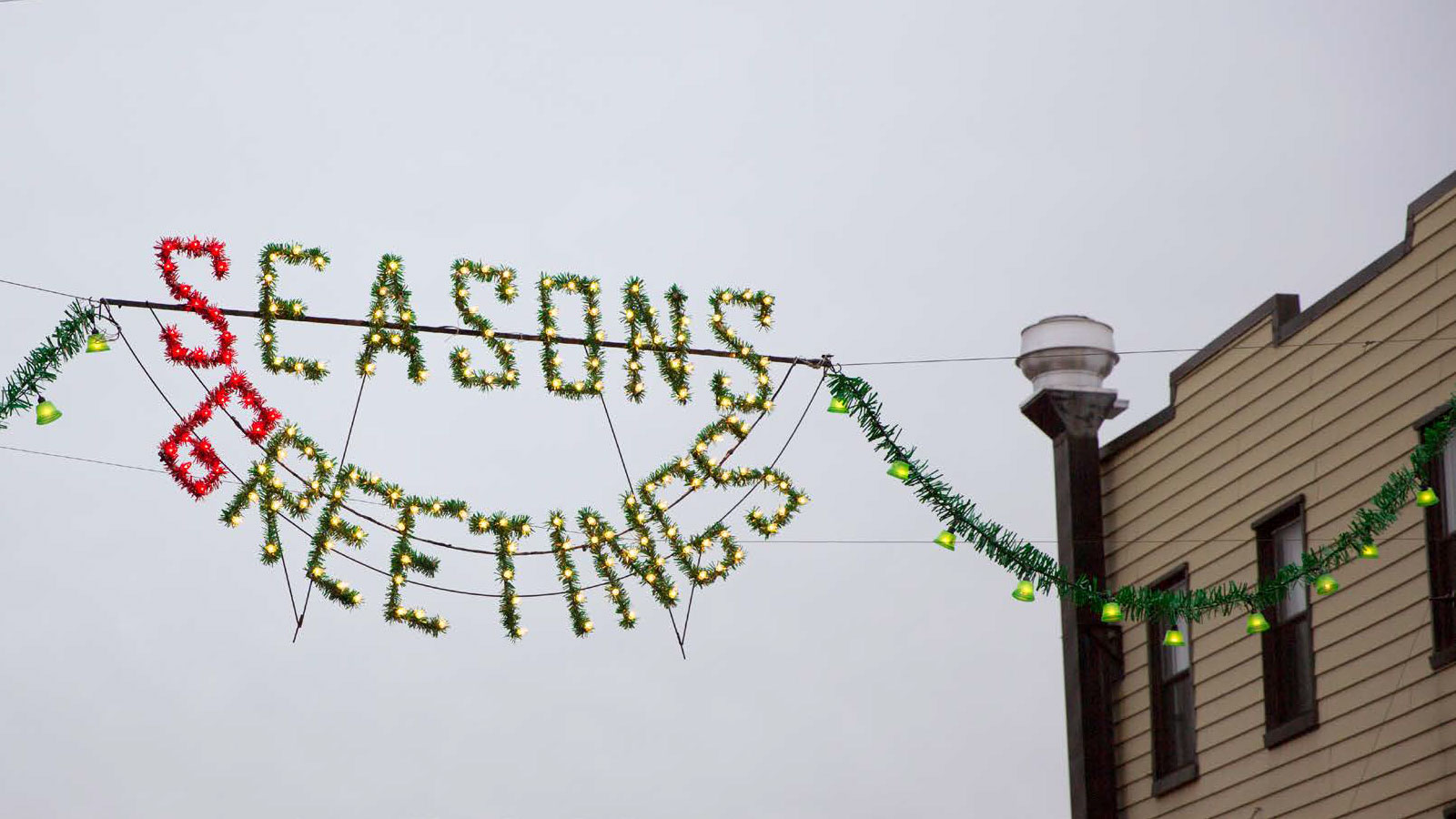 Holiday Season's Greetings banner being hung in the middle of the street of Brooklyn from one building to another.