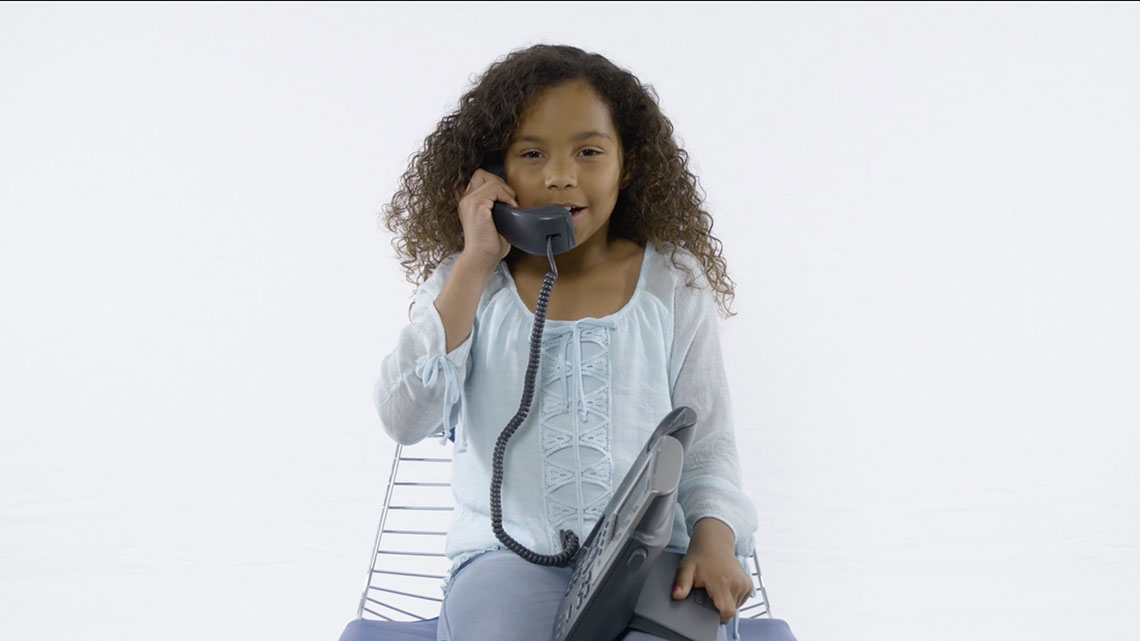 Adolescent child sitting and speaking on the phone.