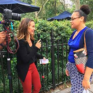 A female reporter interviewing another woman on the street.