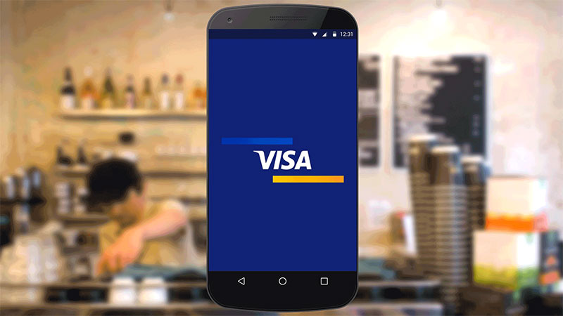 Visa logo displayed on smart phone superimposed over background of a coffee bar counter.