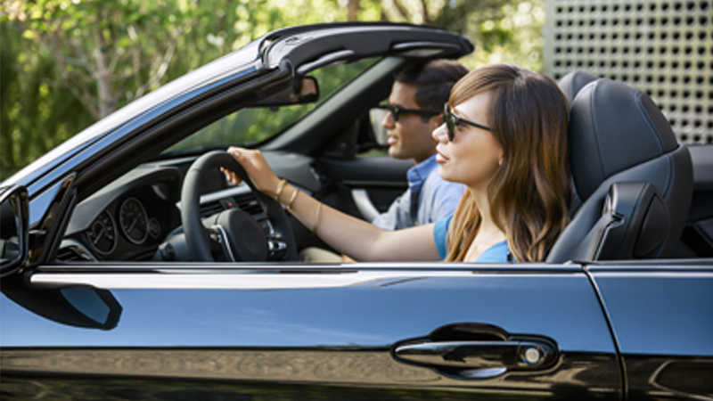 A woman driving a black convertible car and a man in the passenger seat.