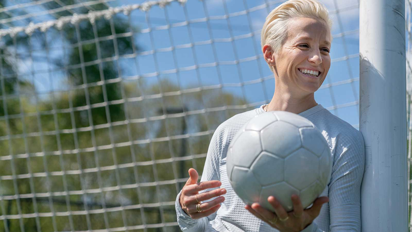 Megan Rapinoe holding a soccer ball while leaning against a goal post.