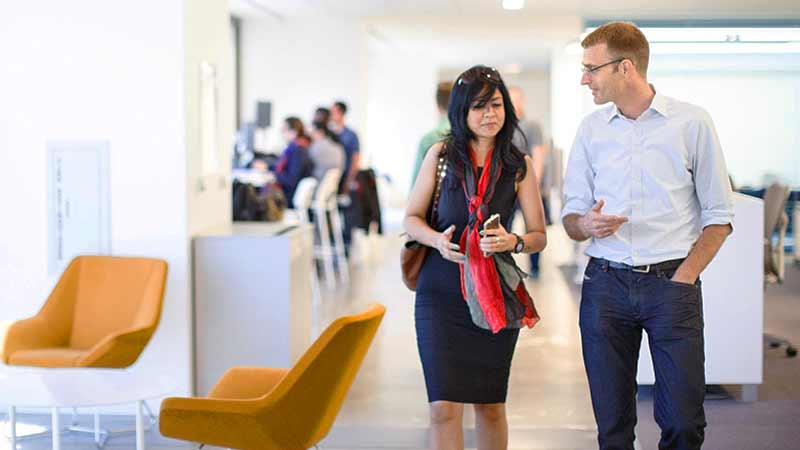 A pair of Visa employees talk while walking through a modern office space.