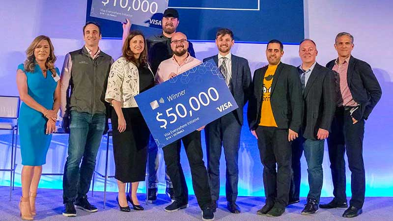 A group of Visa Everywhere Initiative winners pose with an oversized check at an event.