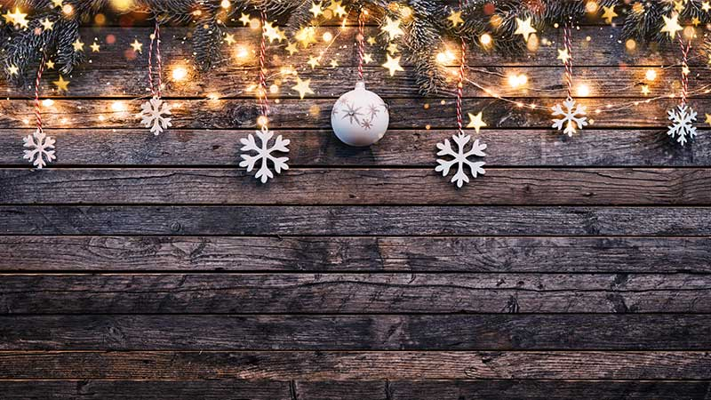 Holiday ornaments and lights hung on a wooden block.
