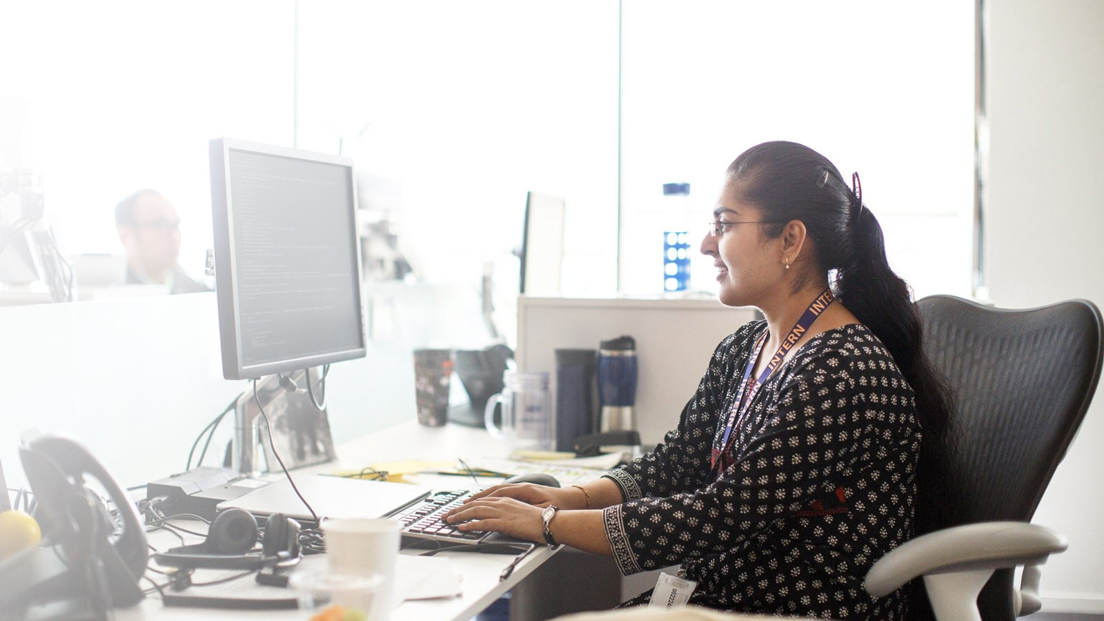 Woman sitting at a desk in an office, working on a computer.