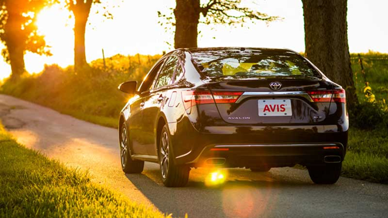 Avis rental car driving on country road at sunset.