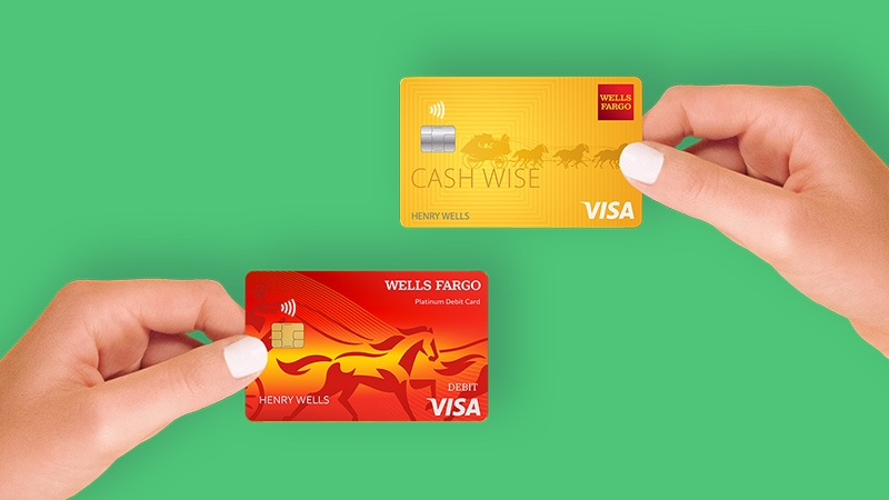 On a green background, a hand on the left holding a Wells Fargo Visa debit card and a hand on the right holding a Wells Fargo Visa credit card.