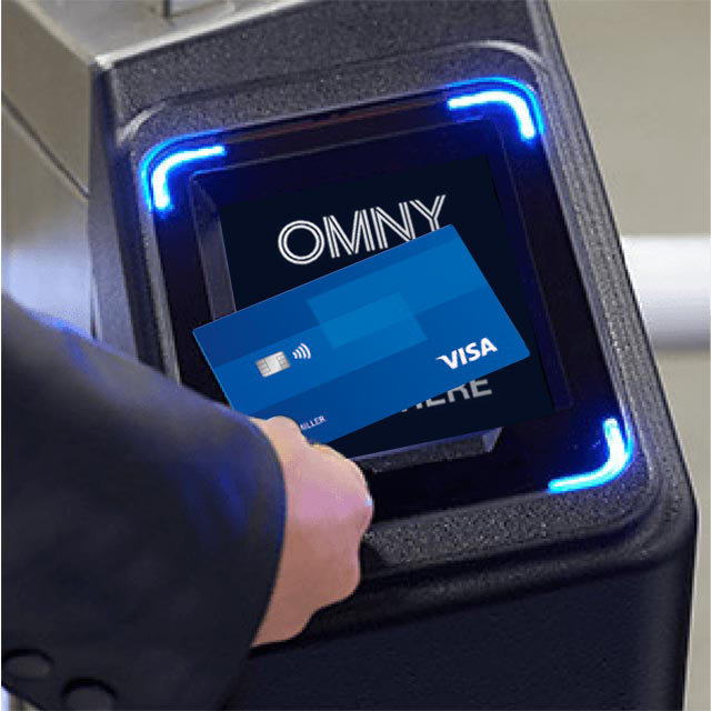 A hand holding a Visa credit card up to an OMNY card reader.