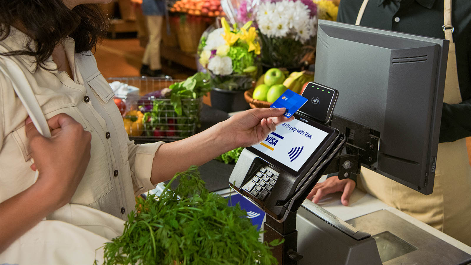Woman tapping to pay at grocery store with Visa card at a Verifone terminal.