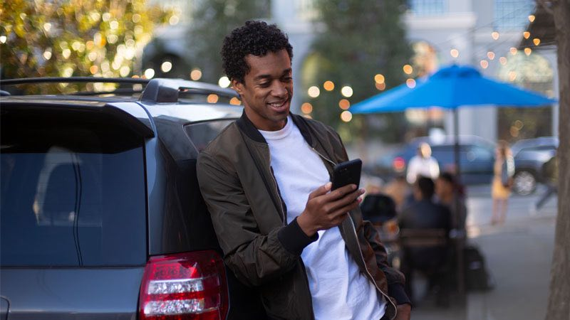 Smiling man leaning against car, looking at his phone.