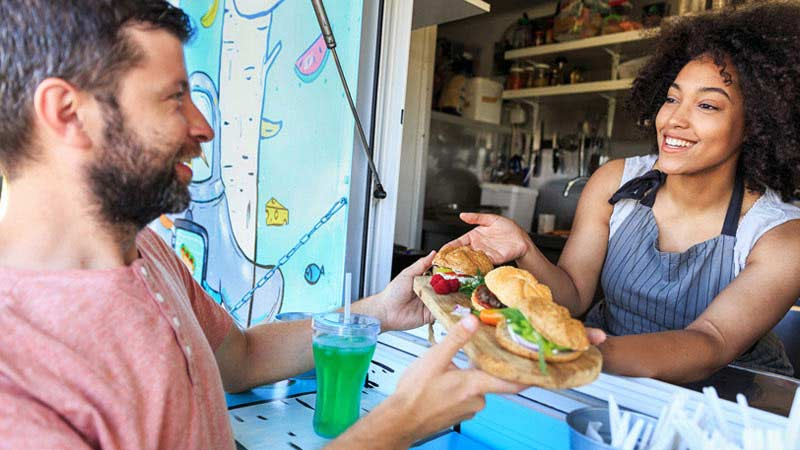 Man ordering hamburger from woman in food truck.