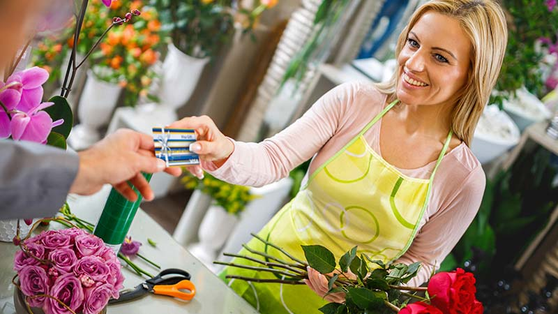 Woman in flower shop with Visa card.