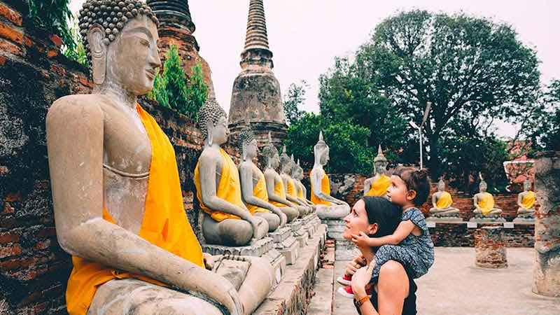 A mother and daughter admire Buddha statues at a temple in Thailand.