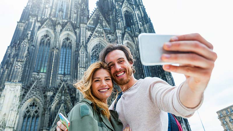A young couple take a selfie in front of the Cologne Cathedral in Germany.